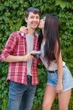 Beaux jeunes couples heureux près de mur vert avec l'appareil-photo regarder l'appareil-photo Image stock