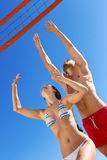 Beaux jeunes couples jouant le volleyball Photo stock