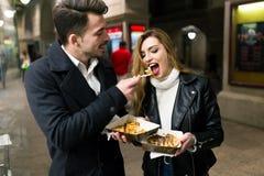Beaux jeunes couples mangeant des gaufres dans la rue Images stock