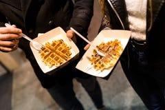 Beaux jeunes couples mangeant des gaufres dans la rue Image libre de droits