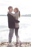Beaux jeunes couples marchant le long de la plage un automne ensoleillé de journée de printemps Images stock