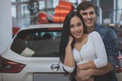 Beaux jeunes couples mariés achetant la nouvelle voiture ensemble image libre de droits