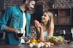 Beaux jeunes couples préparant un repas sain ensemble tout en passant le temps gratuit à la maison photographie stock