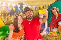 Beaux jeunes couples prenant le selfie contre des tentes Photos stock