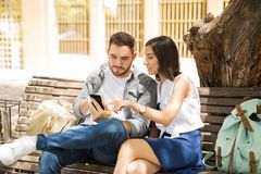 Beaux jeunes couples regardant le téléphone intelligent Image stock