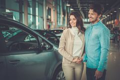 Beaux jeunes couples regardant une nouvelle voiture la salle d'exposition de concessionnaire Photo libre de droits