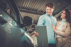 Beaux jeunes couples regardant une nouvelle voiture la salle d'exposition de concessionnaire Photographie stock