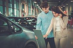 Beaux jeunes couples regardant une nouvelle voiture la salle d'exposition de concessionnaire Photographie stock libre de droits