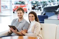 Beaux jeunes couples regardant une nouvelle voiture la salle d'exposition de concessionnaire Image libre de droits