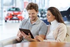 Beaux jeunes couples regardant une nouvelle voiture la salle d'exposition de concessionnaire Images libres de droits