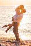 Beaux jeunes couples romantiques embrassant sur le bord de la mer dans les rayons du ri Photo libre de droits