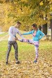 Beaux jeunes couples s'étendant ensemble et se préparant à la course Image stock