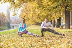 Beaux jeunes couples s'étendant ensemble et se préparant à la course Photo libre de droits