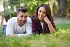Beaux jeunes couples s'étendant sur l'herbe en parc urbain Photos stock