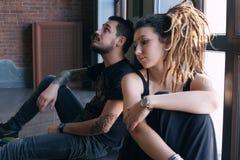 Beaux jeunes couples se reposant de nouveau à sur le plancher près de la fenêtre images libres de droits