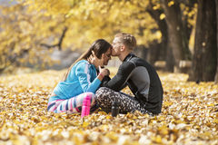 Beaux jeunes couples se reposant et embrassant après la formation réussie en parc Photos libres de droits