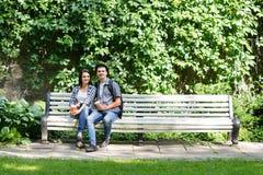 Beaux jeunes couples se reposant sur le banc avec une tasse de café Images libres de droits