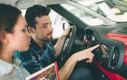 Beaux jeunes couples se tenant au concessionnaire choisissant la voiture pour acheter photographie stock