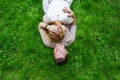 Beaux jeunes couples se trouvant sur l'herbe vert clair images libres de droits