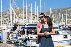 Beaux jeunes couples souriant et étreignant sur un port Image libre de droits