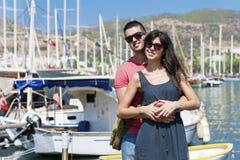 Beaux jeunes couples souriant et étreignant sur un port Photo libre de droits