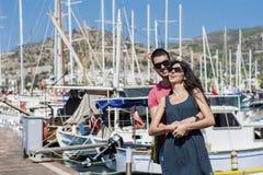Beaux jeunes couples souriant et étreignant sur un port Images stock