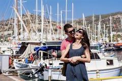 Beaux jeunes couples souriant et étreignant sur un port Photos libres de droits