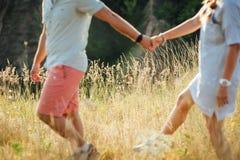Beaux jeunes couples sur un champ au coucher du soleil Image stock