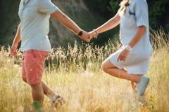 Beaux jeunes couples sur un champ au coucher du soleil Photographie stock libre de droits