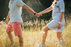 Beaux jeunes couples sur un champ au coucher du soleil Images stock