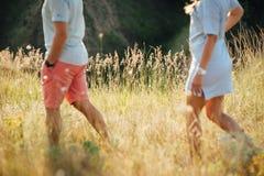 Beaux jeunes couples sur un champ au coucher du soleil Photos stock