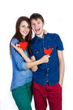 Beaux jeunes couples tenant un petit coeur de papier rouge dans des mains Photographie stock libre de droits