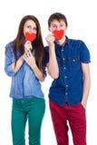 Beaux jeunes couples tenant un petit coeur de papier rouge dans des mains Photo stock