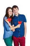 Beaux jeunes couples tenant un petit coeur de papier rouge dans des mains Images stock