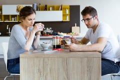 Beaux jeunes couples utilisant le comprimé numérique et le smartphone tout en appréciant le petit déjeuner Photos stock