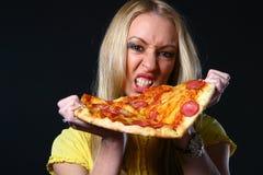 beaux jeunes de femme de pizza de consommation Photographie stock libre de droits