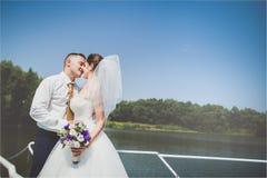 Beaux jeunes mariés élégants sur le yacht de luxe naviguant en bas de la rivière ou du lac leur jour du mariage Photo libre de droits
