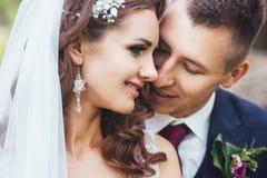 Beaux jeunes mariés de nouveaux mariés étreignant en parc Photographie stock libre de droits