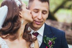 Beaux jeunes mariés de nouveaux mariés étreignant en parc Photo libre de droits