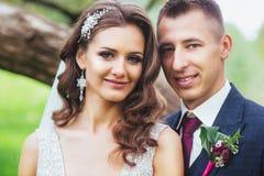 Beaux jeunes mariés de nouveaux mariés étreignant en parc Photo stock