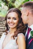 Beaux jeunes mariés de nouveaux mariés étreignant en parc Photos stock