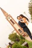 Beaux jeunes mariés devant l'église Photos stock
