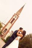 Beaux jeunes mariés devant l'église Images stock