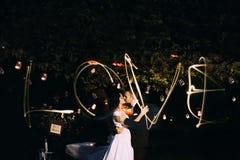 Beaux jeunes mariés embrassant en parc de soirée sous l'arbre décoré de beaucoup de lanternes Mot d'amour de Lightpainted à trave Photo libre de droits