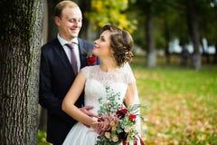 Beaux jeunes mariés en parc un jour ensoleillé Photo stock