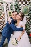 Beaux jeunes mariés espiègles embrassant à leur jour du mariage Plan rapproché photographie stock