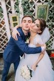 Beaux jeunes mariés espiègles posant dehors à leur jour du mariage Plan rapproché Photos libres de droits