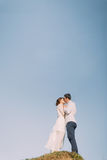 Beaux jeunes mariés heureux embrassant au sommet de la colline contre au ciel Photos stock