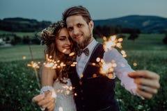 Beaux jeunes mariés sur un pré le soir Photo libre de droits