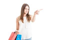 Beaux jeunes shopaholic indiquent la direction gauche avec son fing Photo stock